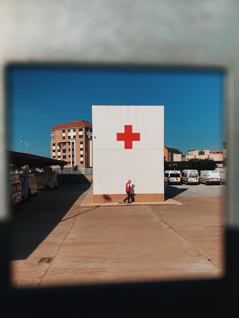 Man walking in front of Red Cross building.