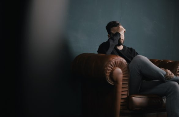Man sitting on the couch looking stressed