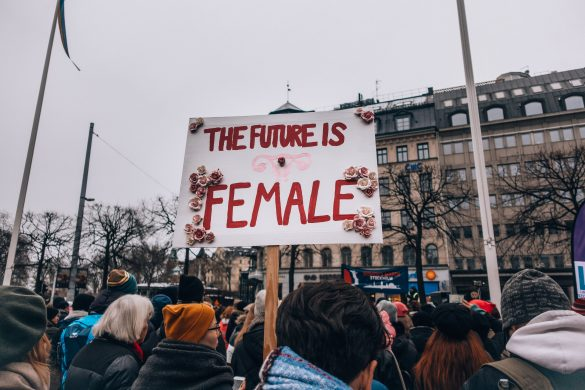 """Woman holding sign saying """"The future is female"""""""