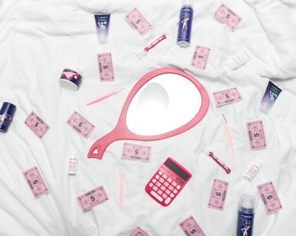 Pink female products laying on a bed.