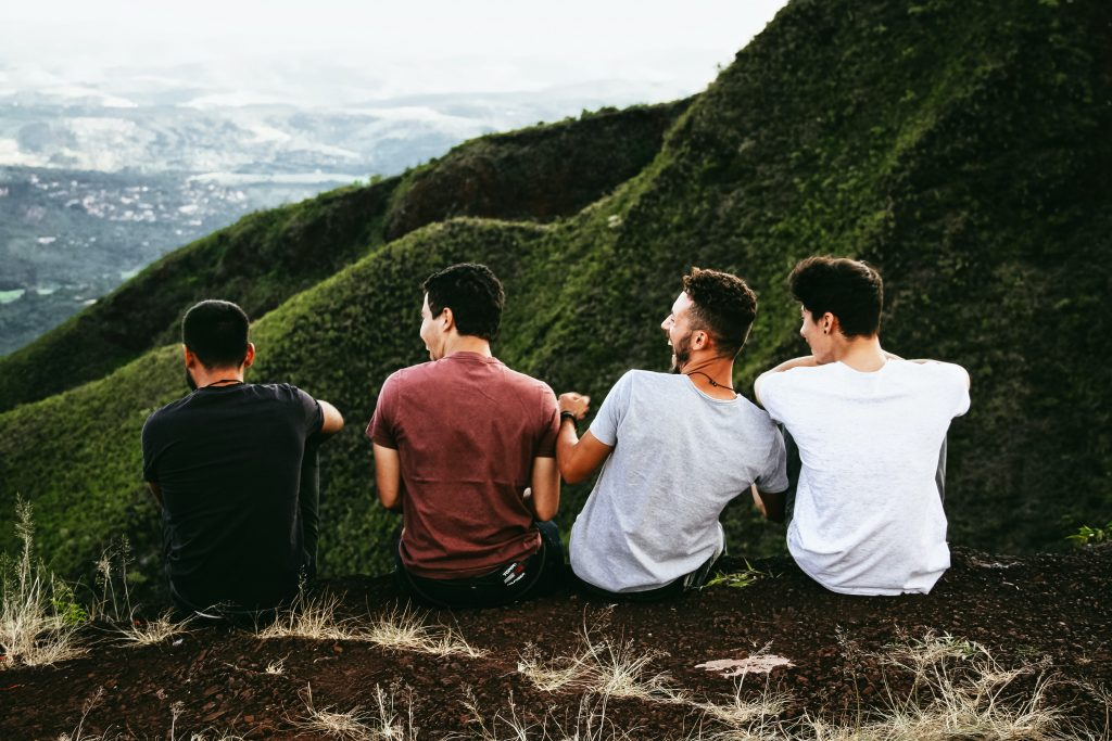 A group of four boys sitting on the edge of a hill, outlooking the valleys of the mountains.
