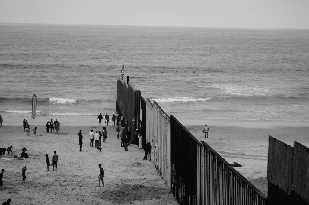 Image of people on a beach at a border wall.
